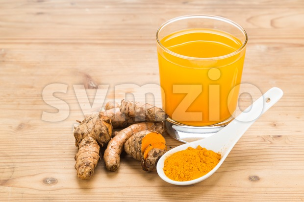 Healthy turmeric roots drinks in a transparent glass on wooden surface. Stock Photo