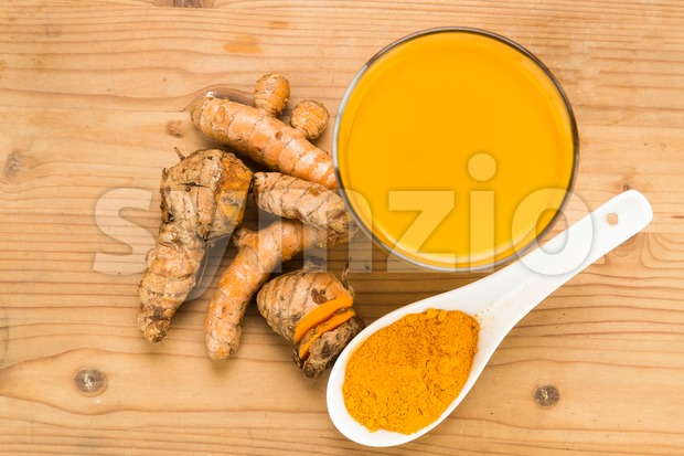Healthy turmeric roots drinks in a transparent glass on wooden surface