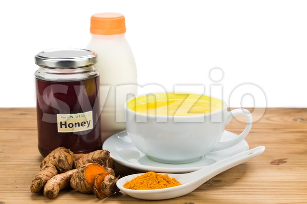 Turmeric roots with milk and honey drinks for beauty and health. Stock Photo