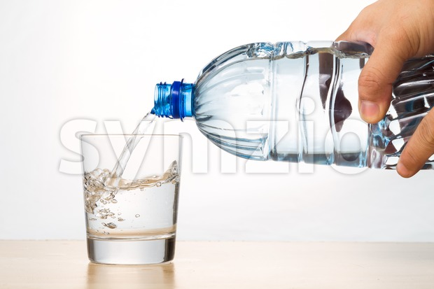 Hand pouring refreshing natural mineral water from bottle into glass Stock Photo