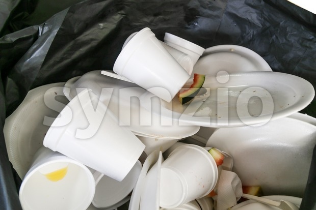 Environmental unfriendly disposed styrofoam plates and cups in garbage bag Stock Photo