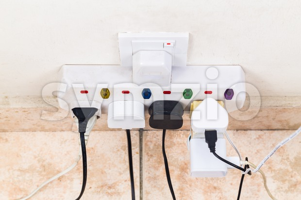 Multiple electricity plugs attached to multi adapter is dangerous Stock Photo