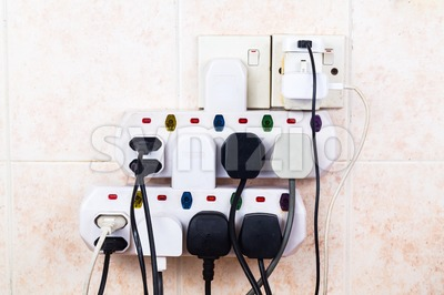Multiple electricity plugs on adapter risk overloading and dangerous Stock Photo