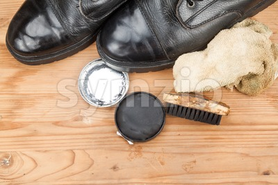 Shoe polish with brush, cloth and worn boots on wooden platform Stock Photo