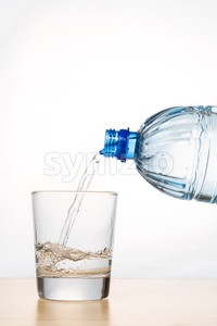 Vertical shot of hand pouring water from bottle into glass Stock Photo