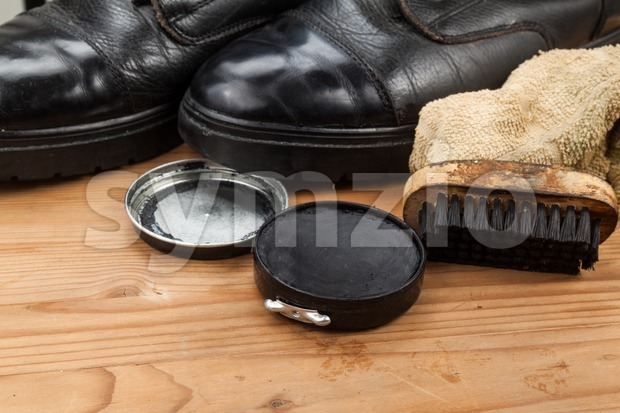 Shoe polish with brush, cloth and worn boots on wooden platform.