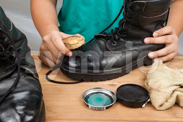 Person polishing a worn out men boots shoe Stock Photo