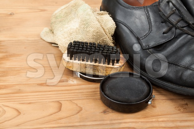 Shoe polish with brush, cloth and worn men shoes on wooden platform.