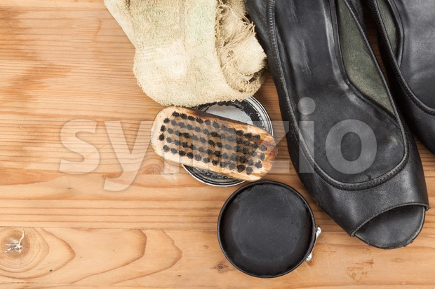 Shoe polish with brush, cloth and worn ladies court shoe on wooden platform.