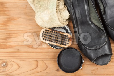 Shoe polish with brush, cloth and worn ladies court shoe on wooden platform Stock Photo
