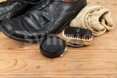 Shoe polish with brush, cloth and worn men shoes on wooden platform Stock Photo