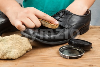 Person polishing and restoring worn out men's formal shoes Stock Photo
