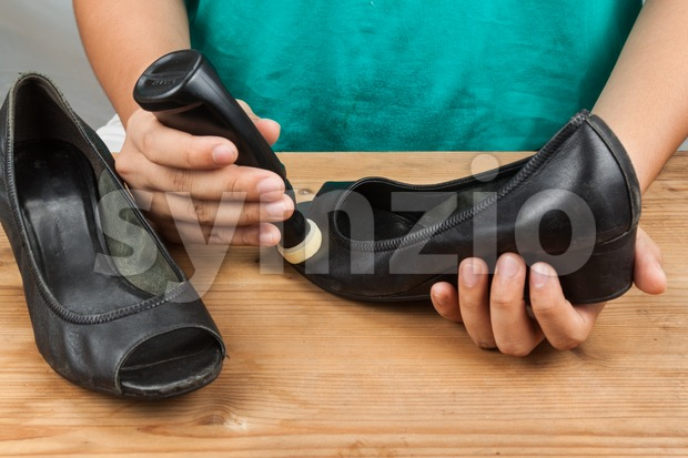 Person polishing and restoring worn out shoe with liquid shoe polish Stock Photo