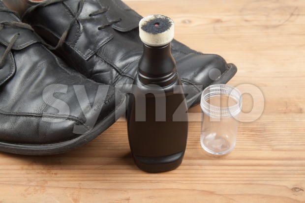 Convenient liquid shoe polish with worn out shoes on wooden platform Stock Photo