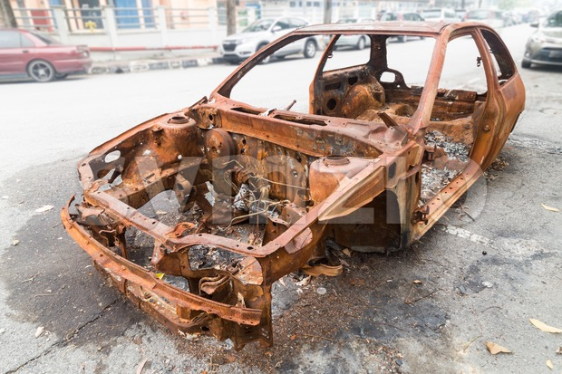 Rusty chassis of a burnt car abandoned by the side of the street. Stock Photo