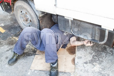 Mechanic under truck reparing dirty greasy oily engine with problem Stock Photo