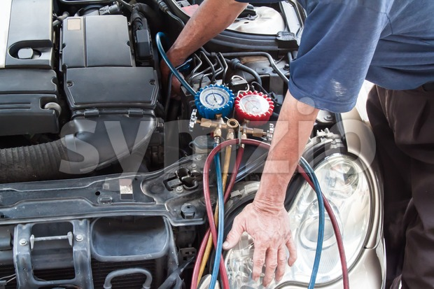 Mechanic with manometer inspecting auto vehicle air-condition compresser with manometer Stock Photo
