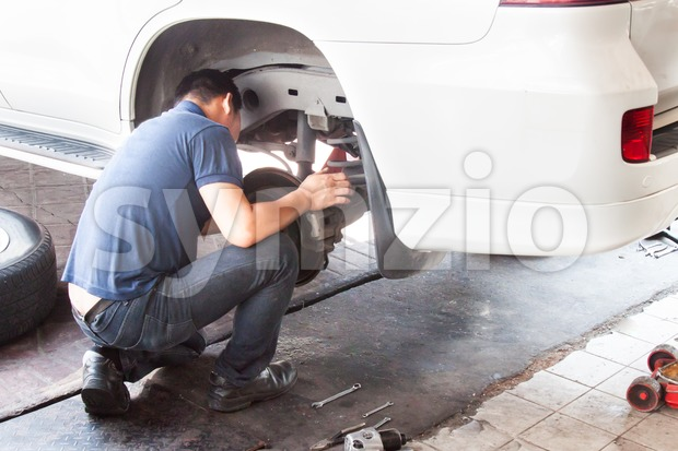 Mechanic inspecting the suspension and brakes of car at workshop Stock Photo