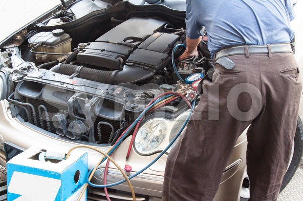 Mechanic with manometer filling gas into auto vehicle air-condition compresser Stock Photo