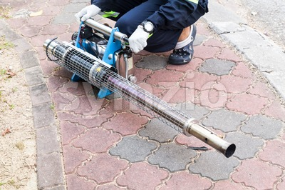 Worker preparing machine to fog with insecticides to kill aedes mosquito, carrier of dengue virus. Stock Photo
