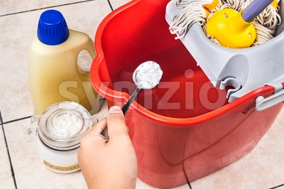 Add baking soda to floor cleaner for house cleaning. Stock Photo