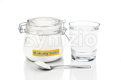 Baking soda in jar, spoonful and glass of water for multiple holistic usages Stock Photo