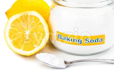 Spoonful of baking soda and lemon fruits for multiple holistic usages. Stock Photo
