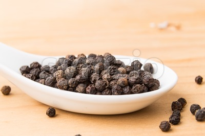 Spoonful of black pepper corns on wooden surface Stock Photo