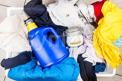 Baking soda with detergent and pile of dirty laundry. Stock Photo