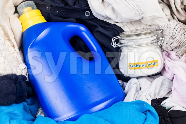 Closeup on baking soda with detergent and pile of dirty laundry. Stock Photo