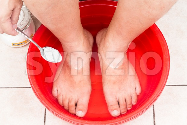 Baking soda being used as feet bath at home. Stock Photo
