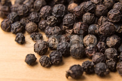 Heaps of black pepper corns on wooden surface Stock Photo