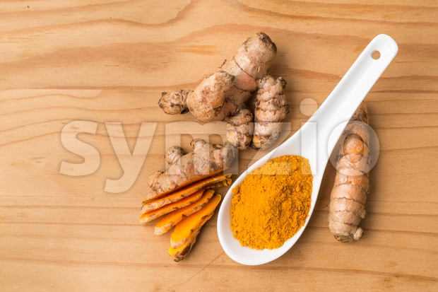 Fresh and grounded aromatic turmeric roots on wooden surface