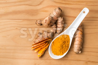 Fresh and grounded turmeric roots on wooden surface Stock Photo
