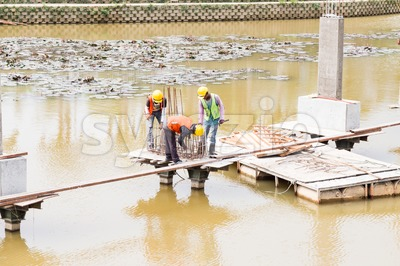 Workers building bridge foundation across lake Stock Photo