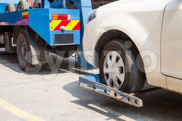 Tow truck towing a broken down car with focus on car being towed. Stock Photo