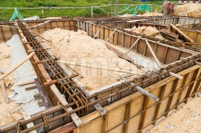 Wooden mold with steel rod forming the foundation beam for infrastructure at construction site Stock Photo