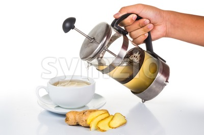 Hand pouring the revitalizing and stimulating hot ginger tea into cup from filter jar Stock Photo