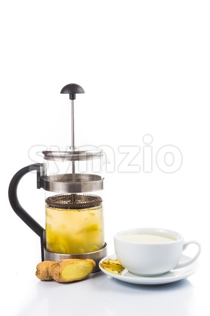 Revitalizing and stimulating hot ginger tea in cup and filter jar Stock Photo
