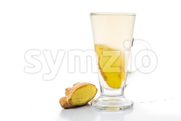 Stimulating hot ginger tea in tall glass with white background