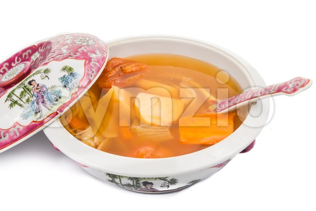 Casserole of potatoes, carrots and tomatoes soup isolated in white. Favorite among Asian of Chinese descent Stock Photo
