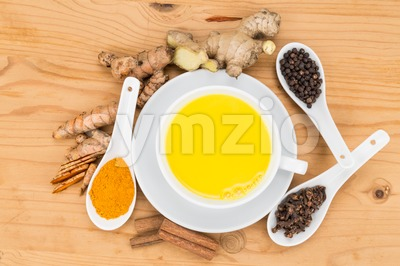 Healthy turmeric milk tea with ginger, cinnamon, cloves, black pepper Stock Photo