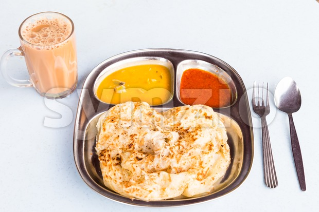 Roti Prata or Roti Canai, a traditional Indian bread served with curry. Goes well with teh tarik or tea with milk. Stock Photo