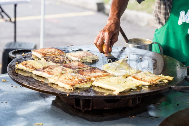 Vendor preparing traditional murtabak cuisine at street bazaar in Malaysia during Muslim fasting month of Ramadan in preparation for iftar