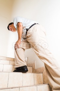 Matured man suffering with knee joint pain climbing stairs Stock Photo