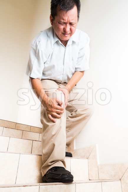 Matured man suffering with knee joint pain descending stairs Stock Photo