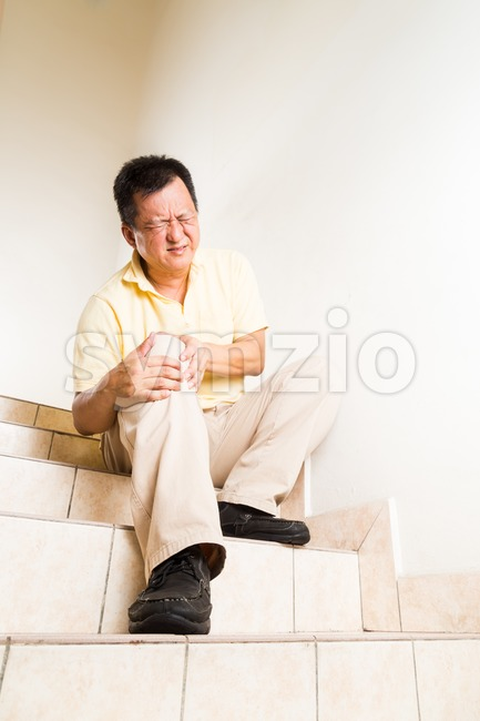 Matured man suffering with acute knee joint pain seated on stairs