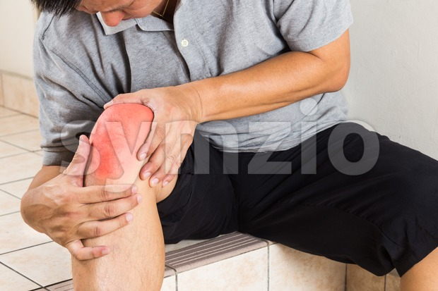 Matured man suffering from painful knee joint seated on steps Stock Photo