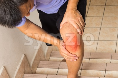 Matured man suffering acute knee joint pain climbing steps Stock Photo