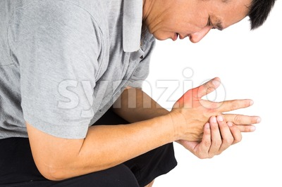 Man with painful and inflamed gout on his hand around the thumb area Stock Photo